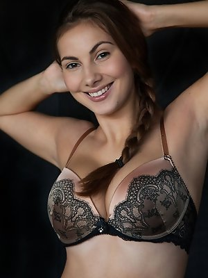 Captivating Connie Carter shows off her dazzling smile and gorgeous svelte body.  Wearing black and tan matching bra and panties, she poses playfully